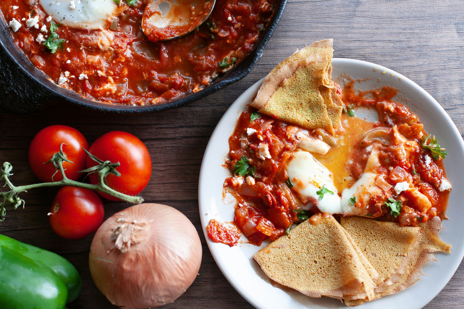 This is a photo of a shakshouka recipe that shows a broken yolk on a plate with the tomato sauce and a low carb wrap.
